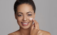 Studio shot of a beautiful young woman applying moisturizer to her face