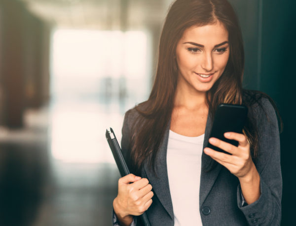 Modern portrait of a young professional business woman checking her phone.