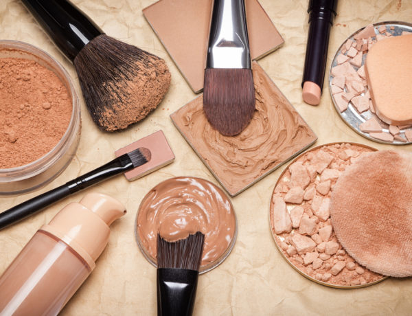 Various makeup products to even out skin tone and complexion on aged paper. Foundation, loose and compact powders, concealer pencil, corrector with brushes and cosmetic sponges. Retro style processing