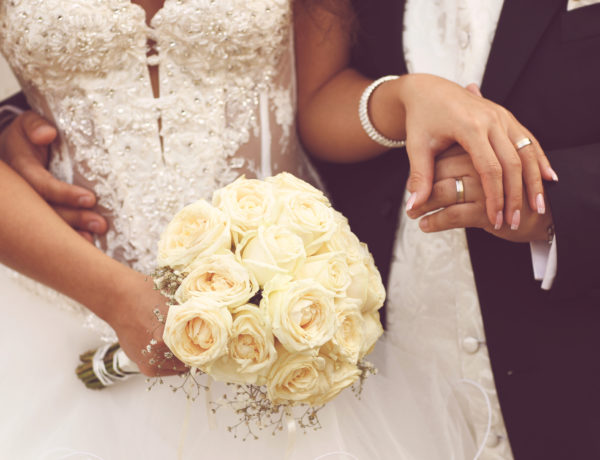 Detail of bride's roses bouquet and hands holding lovely day