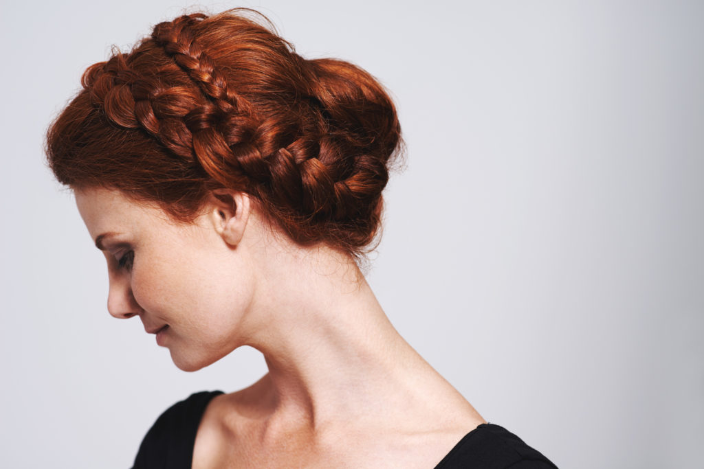 Studio shot of a beautiful redhead woman with a braided up-do posing against a gray background