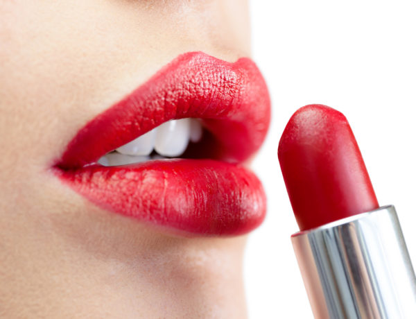 Extreme close up on model on white background applying red lipstick