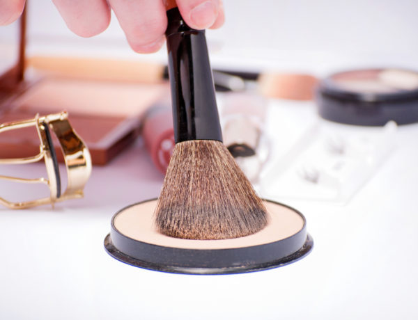 Hand holding a powder brush with cosmetics set