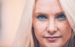 Portrait of a young beautiful caucasian woman with extremely blue eyes with freckles, blond hair, close up, scandinavian woman