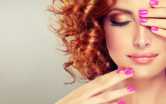 Pretty red haired girl with curls , fashionable makeup and pink manicure.Close up portrait.