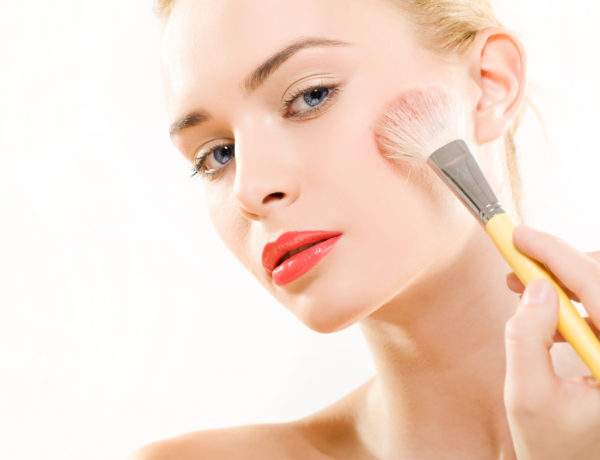 Portrait of beautiful woman model, wich applying make-up skin foundation on white background.