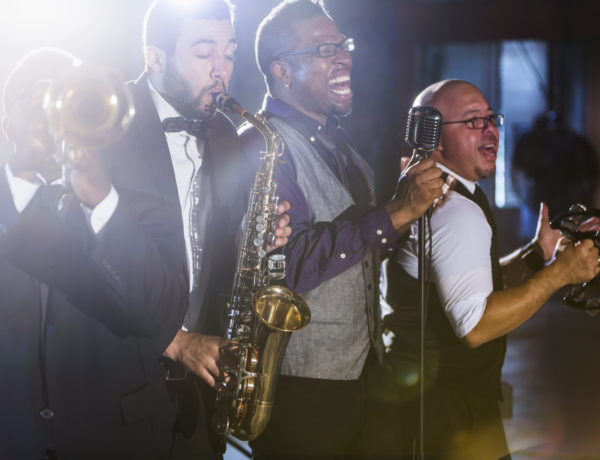 A jazz band performing at a nightclub.  The four male musicians are standing together, playing a trumpet, saxophone, and tambourine.  A mature, African American man is the lead singer, singing into a microphone.