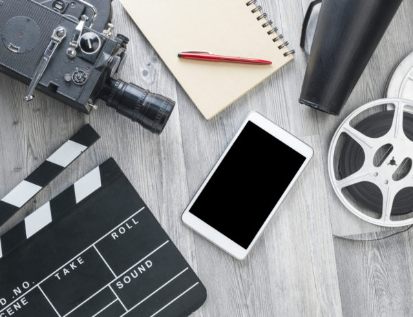 Film slate,movie video camera,notepad,tablet pc,pen,megaphone,film reel and film slate on the gray wooden floor.The photo was shot from directly above view point.The screen of tablet pc and the notepad is blank.No people are seen in frame.Shot with medium format camera Hasselblad in studio.