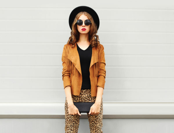 Fashion look, pretty woman wearing a retro elegant hat, sunglasses, brown jacket and black handbag clutch over grey background