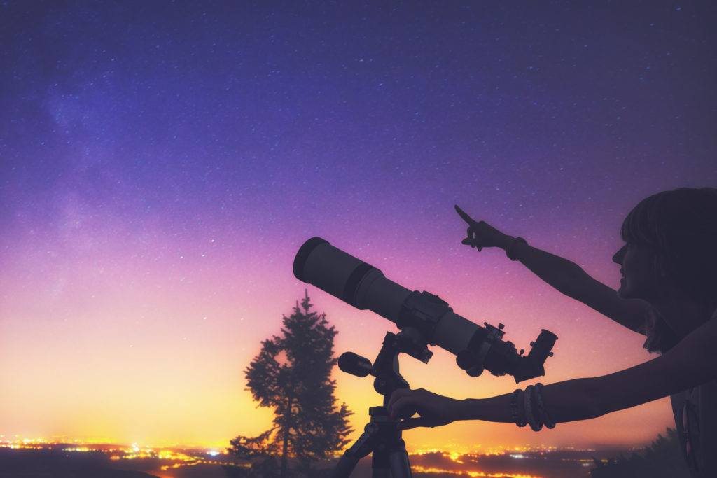 Girl looking at the stars with telescope beside her and de-focused city lights. Milky Way stars and everything else are my work, no elements of NASA or other third party.